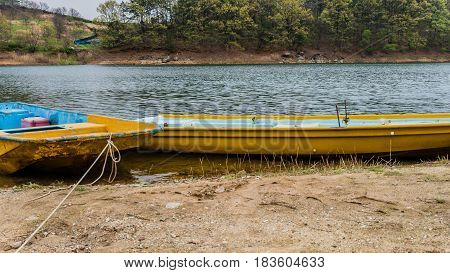 Two yellow metal boats tied up at the shore of a peaceful lake with trees on the far shoreline.