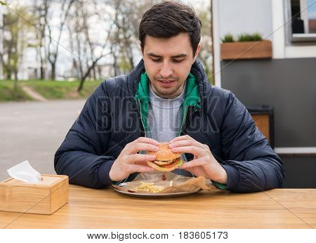 A portrait of young man in street food cafe. He has a great desire to eat a burger. Fast food