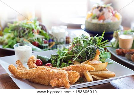 Fish And Chips Deep Fried Battered Fish On A Plate With Chips Close Up And Salat