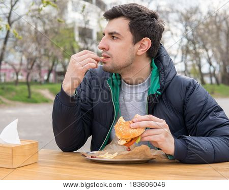 The man is eating French fries in a snack bar. Bitten burger lies on the table.