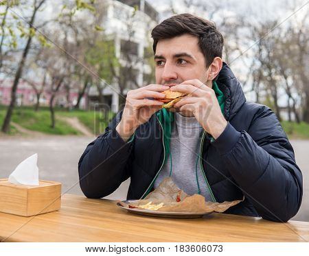 A young man bites off a burger in a snack bar. Street fast food
