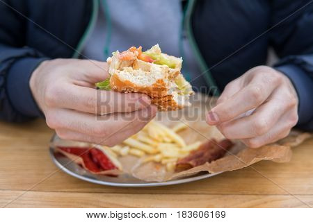 Man's hands holding Bitten burger in a snack bar. French fries lie on the table.