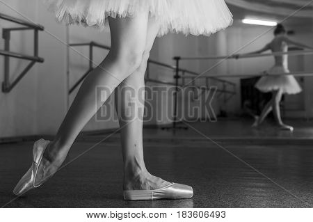 Ballerina in pointes and a pack stretches a foot at the machine. Reflection in the mirror in the ballet class. Classical ballet. Prima ballerina. Shooting close-up. Black and white photography