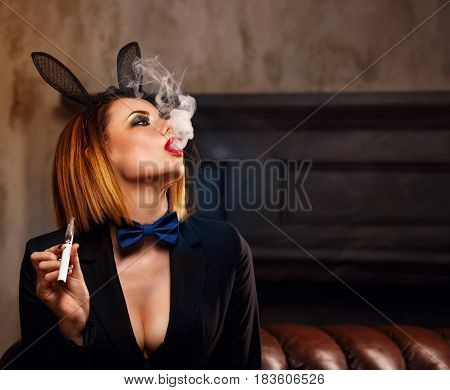 Young attractive girl in a jacket a butterfly tie and bunny ears smokes an electronic cigarette. Femme fatale. Evening makeup smokey eye. She lets out a thick steam from her mouth. Pleasure in vice.