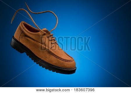 One of flying leather boat shoes of wheat or brown nubuck with flying laces on a blue background for copy space
