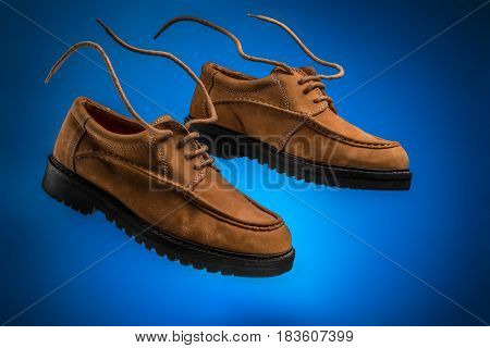 Couple or pair of flying leather boat shoes of wheat or brown nubuck with flying laces on a blue background