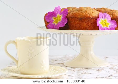 Fresh baked banana muffins with tea in pretty cup with flowers. Horizontal format with shallow depth of field.