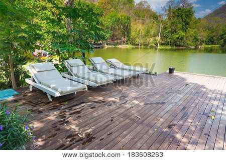 Wooden Deck Chairs On Wood Flooring Near Lake And Mountain Blue Sky