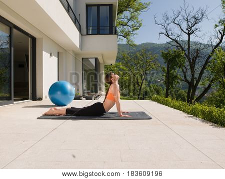 young handsome woman doing morning yoga exercises in front of her luxury home villa