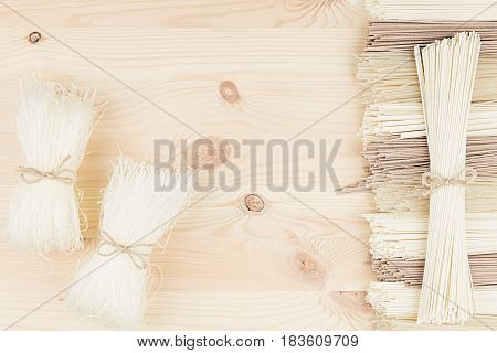 Bundles of raw Chinese noodles on soft beige wooden board with copy space top view.
