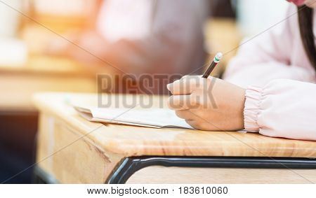 students hand holding pencil fill in Exam carbon paper sheet or test paper on wood desk in classroom at school