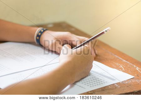 students hand holding pencil fill in Exam carbon paper sheet or test paper on old wood desk in classroom at high school Thailand
