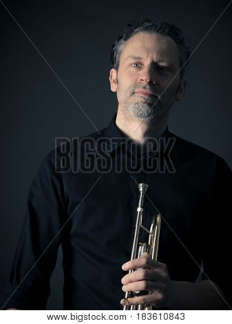Dark portrait of a musician with a brass instrument