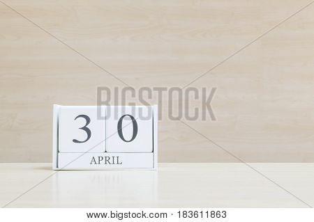 Closeup surface white wooden calendar with black 30 april word on blurred brown wood desk and wood wall textured background with copy space selective focus at the calendar
