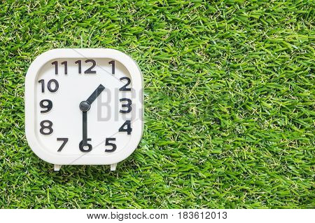 Closeup white clock for decorate show a half past one o'clock or 1:30 p.m. on green artificial grass floor textured background with copy space