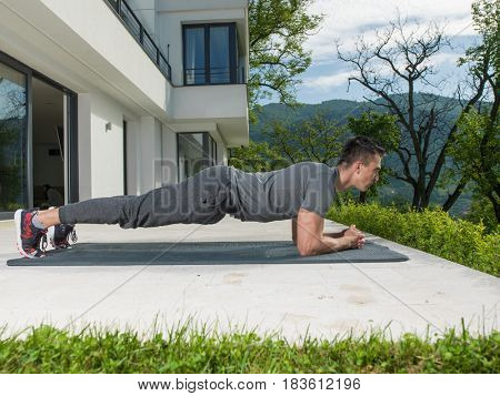young handsome man doing morning yoga exercises in front of his luxury home villa