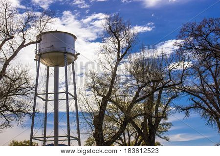 Water Tower Against Blue Sky & Tree Limbs