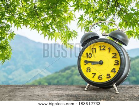 Closeup black and yellow alarm clock for decorate show a quarter to nine o c'clock or 8:45 a.m. on blurred leaves and mountain view background