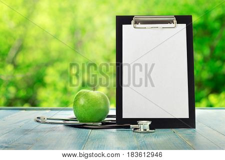 Clipboard with green apple and stethoscope on a blue wooden table against the background blur green leaves bokeh
