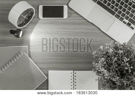 Closeup space of brown wood desk with light from small lamp in the dark room with blurred computer book and mobile phone textured background in black and white tone and top view
