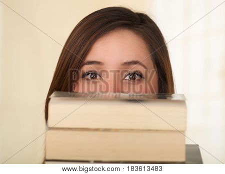 Young Pretty Woman Hiding behind a book.