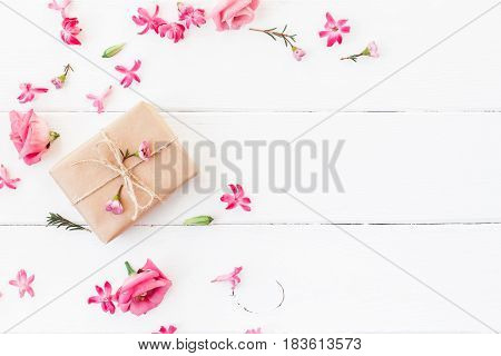 Flowers composition. Gift and pink flowers on white wooden background. Flat lay top view
