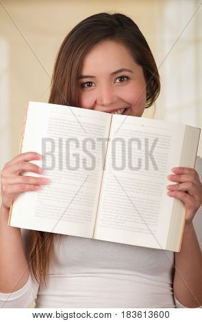 Young Pretty Woman Hiding Behind Open Book.