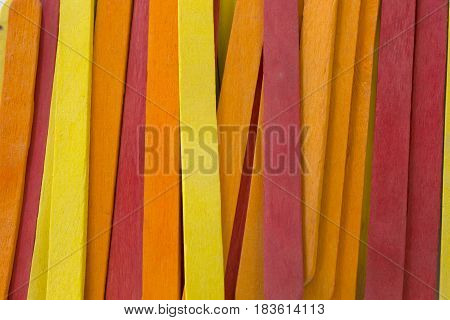 This is a photograph of Red,Yellow and Orange colored popsicle sticks background