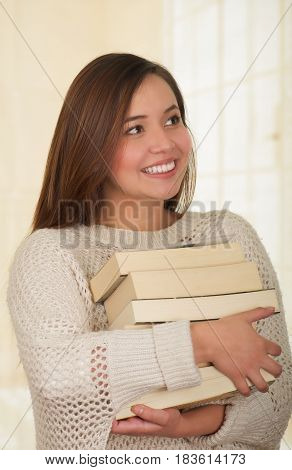 Woman holding pile of books, close up.