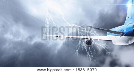 Airplane flying in stormy sky . Mixed media