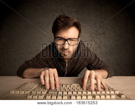 A young hacker with glasses dressed in casual clothes sitting at a desk and working on a computer keyboard in front of black clear concrete wall background concept