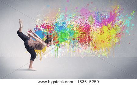 A funky contemporary hip hop dancer dancing in front of grey background with colorful bright paint splatter concept