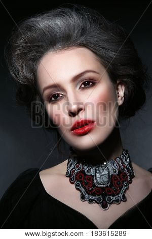 Vintage style portrait of young beautiful woman with gothic make-up and fancy contact lenses