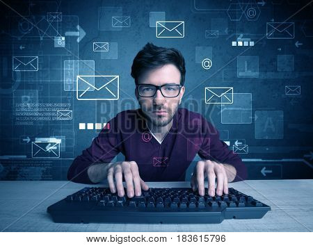 A talented young hacker hacking email address passwords concept with keyboard on desk and illustrated letters in the background