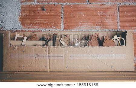 Wooden rims for glasses in cardboard box standing on shelf in workshop.