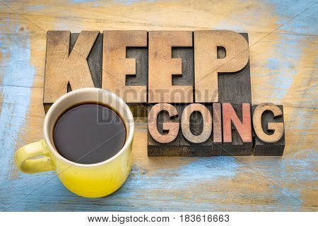 Keep going motivation word abstract in vintage letterpress wood type blocks with a cup of coffee