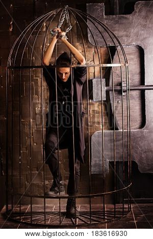young men in black cloth in metal cage
