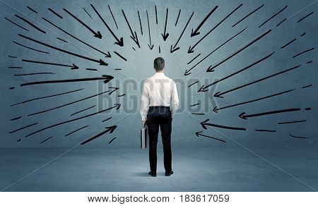 A confused businessman under pressur after making a bad decision illustrated with drawn arrows pointing at him in clear blue urban space concept