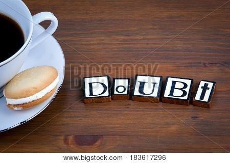 Doubt text on a wooden background. Coffee with a tasty and sweet biscuits