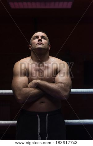 portrait of muscular professional kickboxer with arms crossed in the ring