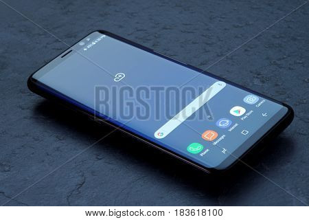 Koszalin, Poland - 25 April, 2017: Black Samsung Galaxy S8 on stone table. Samsung S8 are new generation smartphone from Samsung. The Samsung S8 is smart phone with multi touch screen