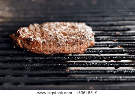Beef Burgers And Spatula On The Hot Flaming BBQ Charcoal Grill, Close-up.
