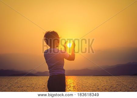 Sun on female hand. Silhouette of hand holding sun / Portrait of young woman as silhouette and hand holding the sun