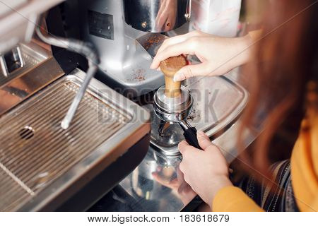 small business, people and service concept - woman or waiter in apron with holder and tamper preparing coffee at coffee shop.