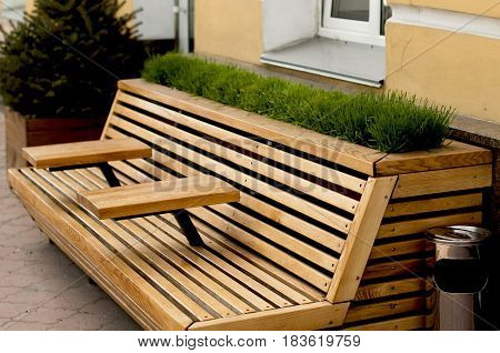 Modern wooden bench with armrest table and decorated with lawn grass