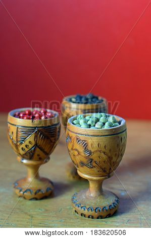 Green, pink and black peppercorns in wooden glass. Vertical image.