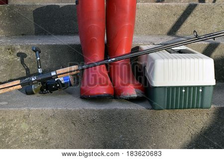 Fishing equipments. Fishing reel, red rubber boots and tackle box on stairs.