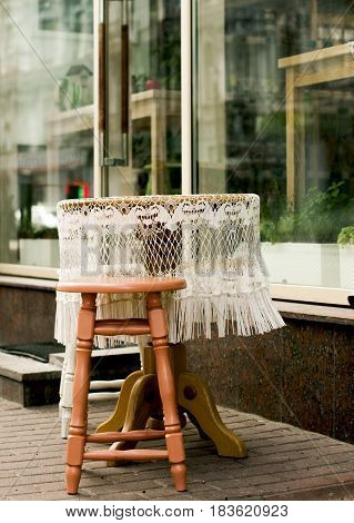 Street exterior. Small round table with white lace tablecloth near the showcase of a street cafe