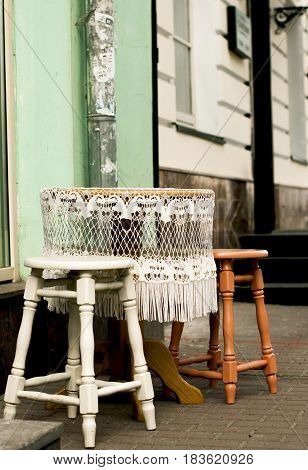 Round table with white lace tablecloth and two chairs on each side outdoor
