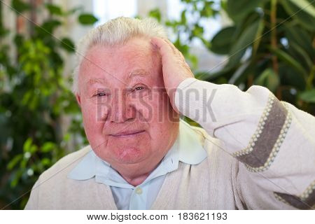 Picture of an elderly man having a headache at home